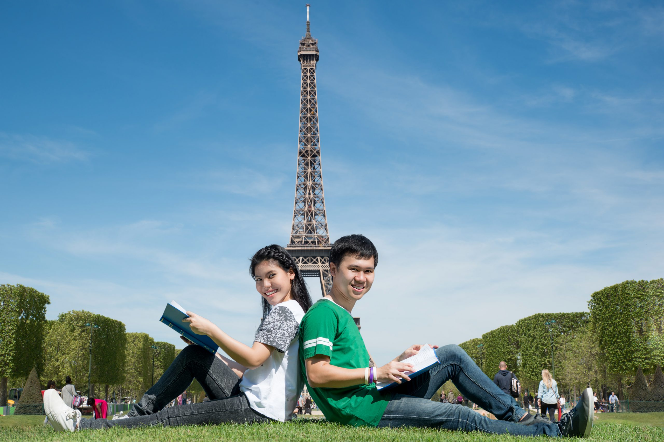 asian-couple-student-reading-book-together-outdoors-park-near-eiffel-tower-paris-france-scaled-1